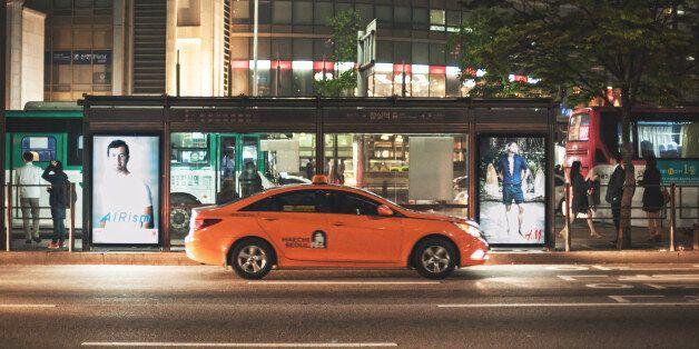 Seoul, Republic of Korea - May 12, 2014: Orange taxis cruising the streets at night Jamsil