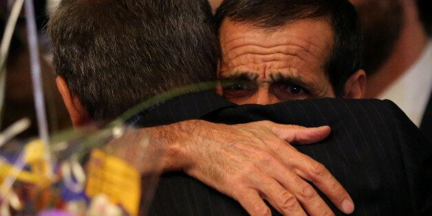 Iranian Ali Vayeghan hugs his brother Hossein as he arrives at Los Angeles International airport after...