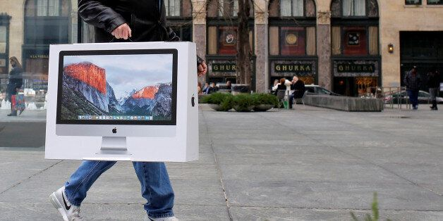 A man carries a newly purchased iMac from the Apple Fifth Avenue store during Black Friday sales in Manhattan,...
