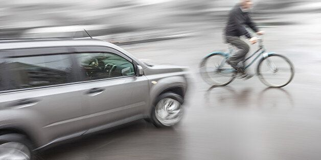 Dangerous city traffic situation with a cyclist and cars in motion