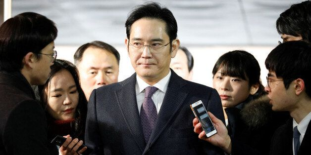 Samsung Group chief, Jay Y. Lee, is surrounded by media as he arrives at the Seoul Central District Court...