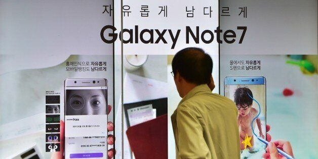 A man speaks over his phone in front of a signboard of the Samsung Galaxy Note7 at a Samsung showroom...