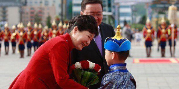 South Korea's President Park Geun-hye (L) is greeted by a Mongolian boy as Mongolia's President Tsakhiagiin...