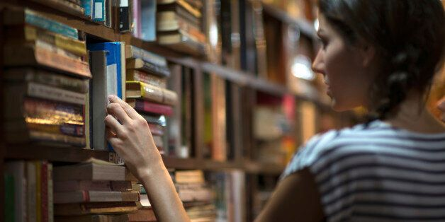 Beautiful woman looking at books in a library. Ambient light to emphasize the mood and location. Converted...