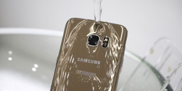 A model demonstrates the waterproof function of a Samsung Electronics' new smartphone Galaxy S7 Edge...