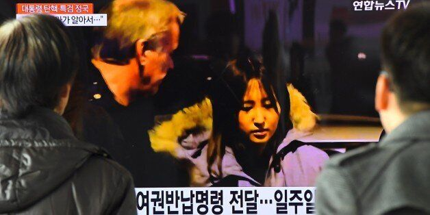 People watch a screen showing a news report on the arrest of Chung Yoo-Ra (C), the 20-year-old daughter...