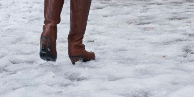 Woman with brown leather boots walks on icy street in