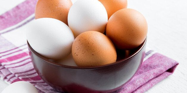 Raw organic brown and white eggs in bowl over linen napkin and wooden