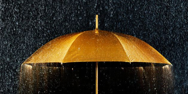 Conceptual photograph of a golden umbrella with