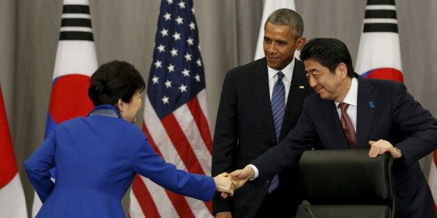 U.S. President Barack Obama stands behind as South Korean President Park Geun-Hye (L) and Japanese Prime...