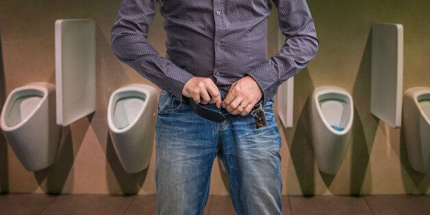 Man zip his pants up after peeing on the public toilet in