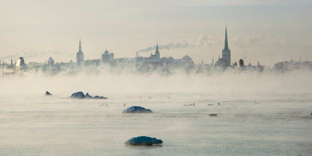 Cityscape of Tallinn over the waterfront in a cold day. -18 degrees Celsuis. The sea is steaming cause...
