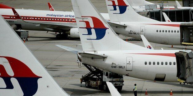 Malaysia Airlines ground staff walk past Malaysia Airlines aircraft parked on the tarmac at the Kuala...