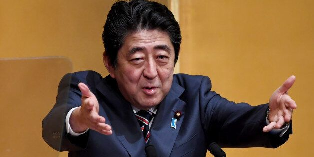 Japanese Prime Minister Shinzo Abe gestures while delivering his speech at a lecture hosted by the Naigai...