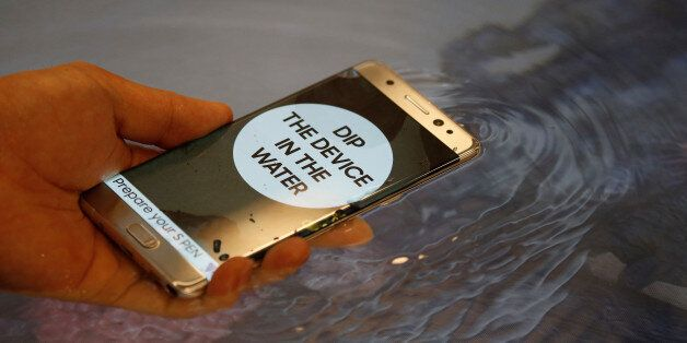 FILE PHOTO - A model demonstrates waterproof function of Galaxy Note 7 new smartphone during its launching...