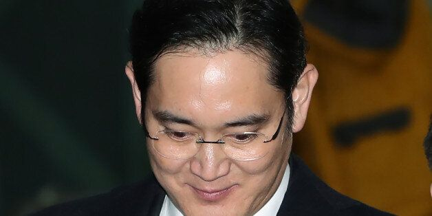 Jay Y. Lee, co-vice chairman of Samsung Electronics Co., center, is surrounded by members of the media...