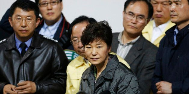 South Korean President Park Geun-hye (C) listens to a family member of a missing passenger who was on...