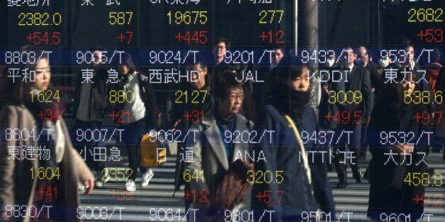 Pedestrians are reflected in an electric quotation board flashing stock prices on the Tokyo Stock Exchange...