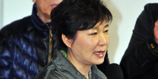 South Korea's President Park Geun-Hye (C) speaks during a visit to relatives of missing passengers on...