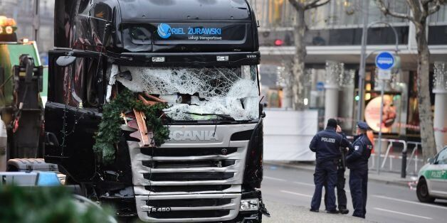 Policemen stand next to a truck on December 20, 2016 at the scene where it crashed into a Christmas market...