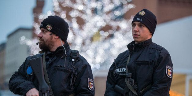 Armed policemen stand at the christmas market in Schwerin, northern Germany, on December 20, 2016 one...