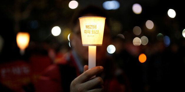 A man holds a candlelight bearing a message that
