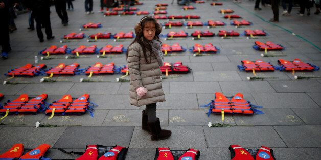 A girl stands between life vests symbolising the 304 victims of sunken ferry Sewol during a protest demanding...