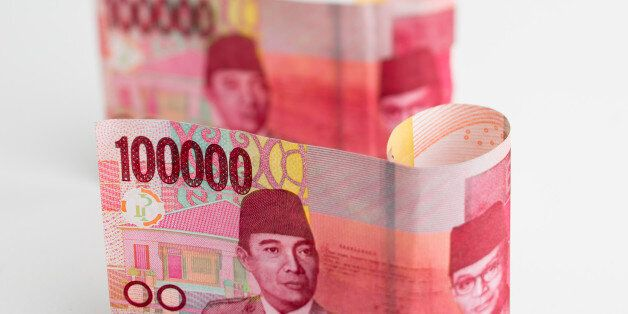 Indonesian 100,000 rupiah banknotes are arranged for a photograph in Bangkok, Thailand, on Tuesday, Sept....