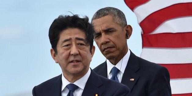 US President Barack Obama (R) listens as Japanese Prime Minister Shinzo Abe speaks at the USS Arizona...