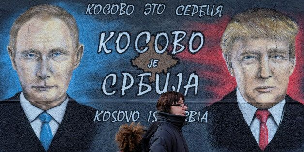 A woman with a child walks past a mural of U.S. president-elect Donald Trump and Russian President Vladimir...