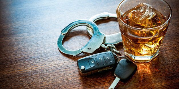 Whiskey with car keys and handcuffs concept for drinking and