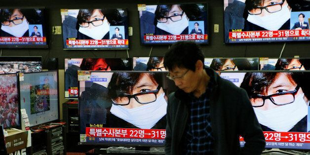 An employee watches TV sets broadcasting a news report on Choi Soon-sil, a long-time friend of South...