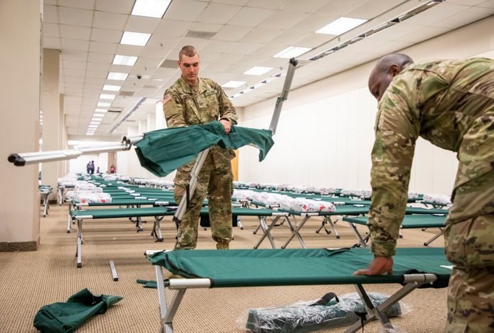 US Army National Guard Pvt. Christopher Zambuto, left, and Specialist Jermaris Hamilton assemble cots in a shelter for Hurric