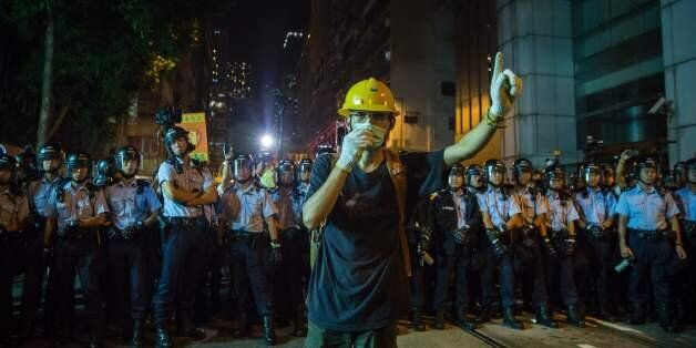 A protester wearing a mask gestures in front of riot police amid ongoing demonstrations in Hong Kong...