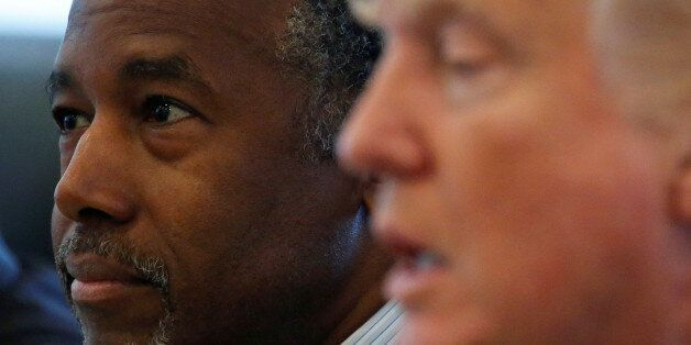 Ben Carson (L) and Republican presidential then nominee Donald Trump speak during a round table with...