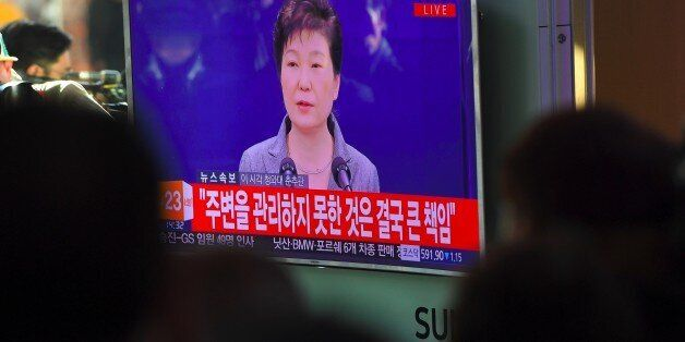 People watch a television news live showing South Korean President Park Geun-Hye making a speech, at...
