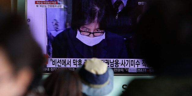 SEOUL, SOUTH KOREA - NOVEMBER 03: South Koreans watchs a television broadcast reporting the political...
