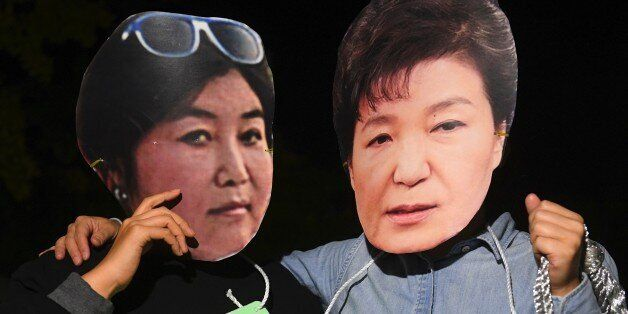 Protestors wearing masks of South Korean President Park Geun-Hye (R) and her confidante Choi Soon-Sil...