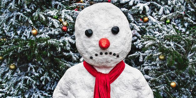 A snowman stands in front of a Xmas tree with a sad