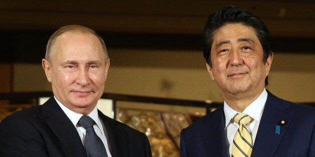 JAPAN, NAGATO - DECEMBER 15: (RUSSIA OUT) Russian President Vladimir Putin (L) shakes hands with Japanese...