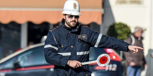 A police officer controls cars and scooters during the limited traffic day, in centeral Rome, on December...