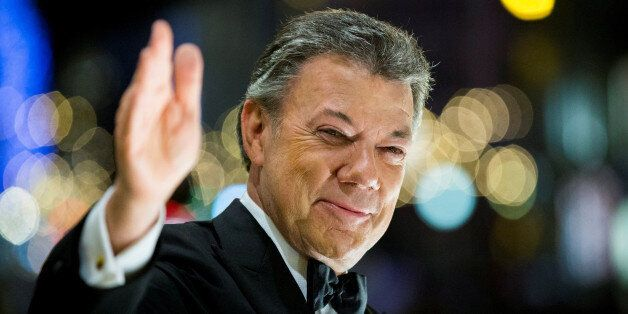 Nobel Peace Prize laureate Colombian President Juan Manuel Santos reacts to the torchlight parade from...