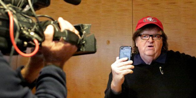 NEW YORK, NY - NOVEMBER 12: Filmmaker Michael Moore films himself with a smartphone at Trump Tower on...
