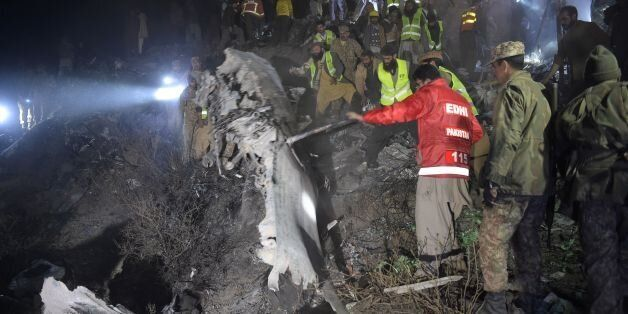 Pakistani soldiers and volunteers search for victims from the wreckage of the crashed PIA passenger plane...