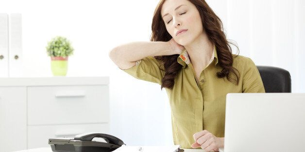 Young Businesswoman Having Neckache in the office, doing massage of the neck and sitting at the