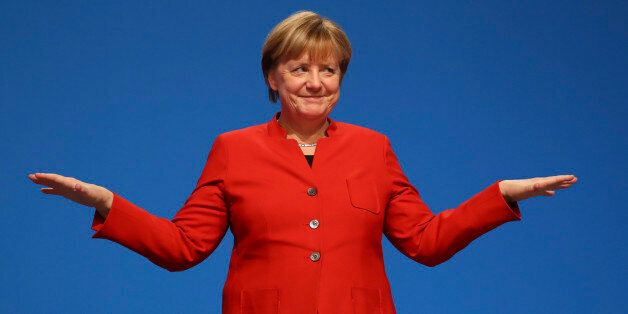 German Chancellor and leader of the conservative Christian Democratic Union party CDU Angela Merkel reacts...