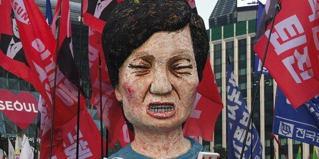 Protesters carry an effigy of South Korea's President Park Geun-Hye during an anti-government rally demanding...