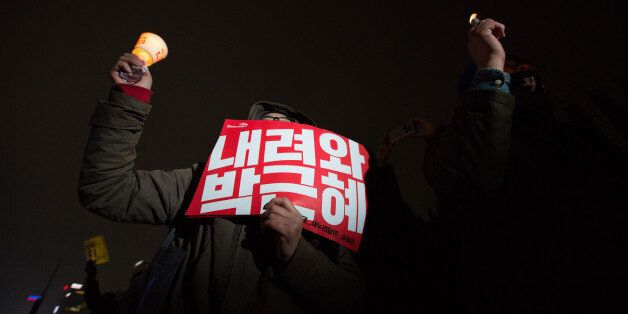 A protester holds a candle and a placard during a rally in Seoul, South Korea, on Saturday, Nov. 26,...