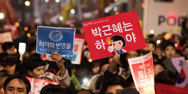 Protesters hold placards during a rally in Seoul, South Korea, on Saturday, Nov. 26, 2016. Hundreds of...