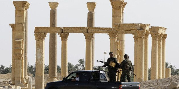 Members of the Syrian army patrol as people visit the the ancient Syrian city of Palmyra on May 6, 2016,...